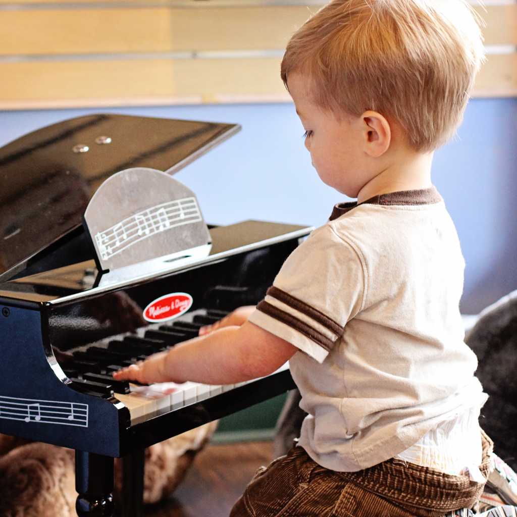 baby-boy-playing-childs-piano-in-the-store-window