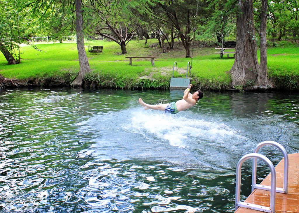 guy-swinging-on-tree-rope-ring-into-blue-hole